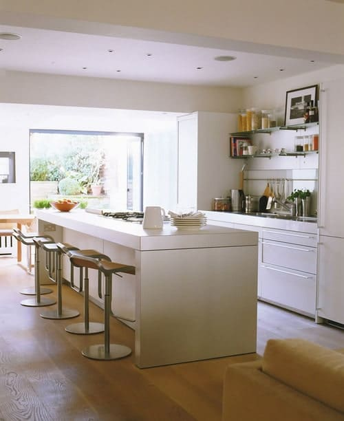 A bright kitchen setup featuring built-in shelves and a white kitchen counter along with a white island with space for a breakfast bar.