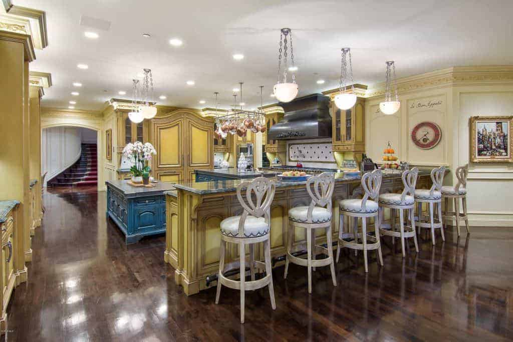 Large yellow kitchen featuring two islands and a long breakfast bar counter lighted by charming pendant lights.