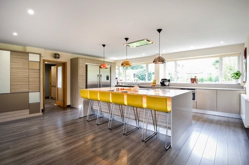 This kitchen features hardwood floors and a regular white ceiling. The kitchen offers a large center island with space for a breakfast bar paired with yellow seats.