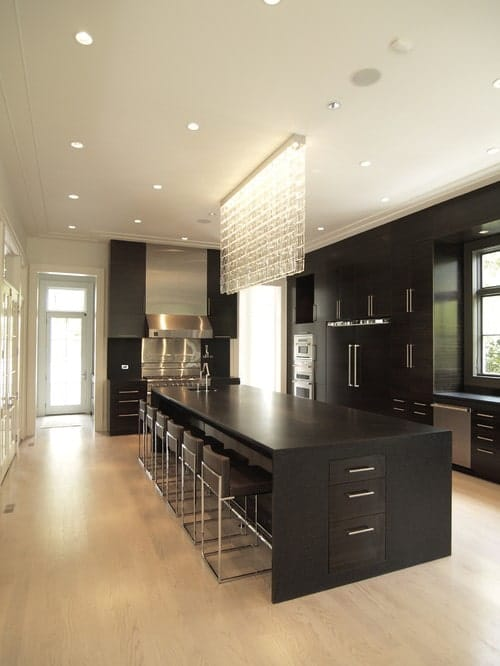 This kitchen offers a large and long center island finished in black and has space for a breakfast bar paired with modern bar seats and is lighted by a glamorous ceiling lighting.