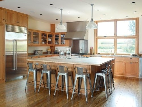 A brown kitchen featuring hardwood floors and wooden cabinetry and kitchen counters. The center island offers space for a breakfast bar lighted by a couple of pendant lights.