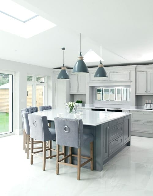A bright kitchen featuring a white ceiling and white tiles flooring along with a gray center island, bar seats and pendant lights.