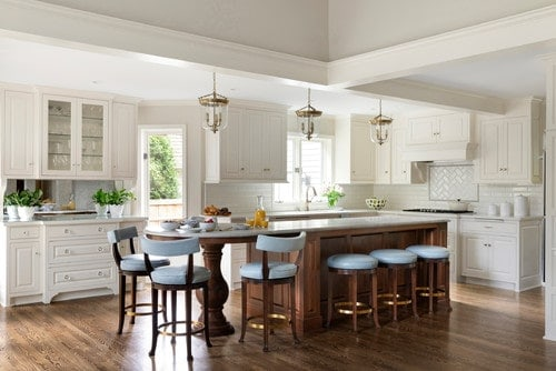 A spacious kitchen featuring a beautiful island with a breakfast bar lighted by charming pendant lights.