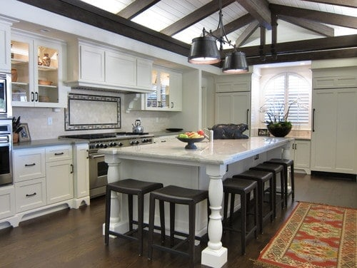 This kitchen features hardwood flooring and a vaulted ceiling with exposed beams, along with a large center island with a marble countertop and has space for a breakfast bar.