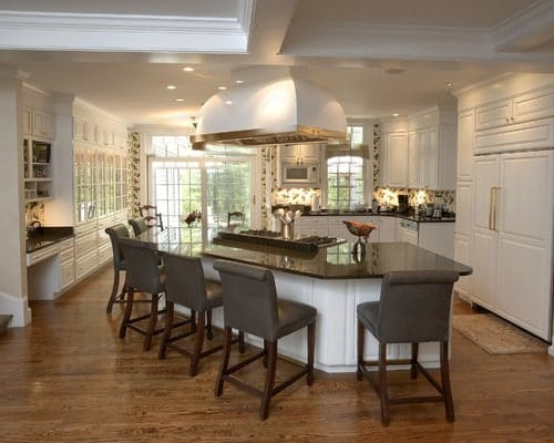This kitchen boasts a custom island with a breakfast bar. The area has hardwood floors and a white ceiling.