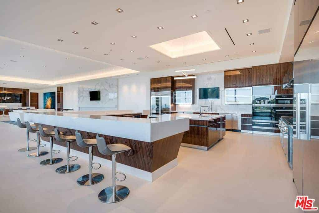 Spacious contemporary kitchen featuring a thick white countertop on the breakfast bar counter. The ceiling boasts multiple ceiling lights as well.