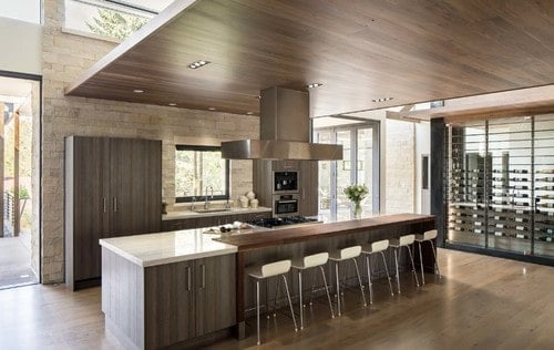 A single wall kitchen featuring hardwood flooring and a wooden ceiling. It also has a center island with a wooden breakfast bar counter.