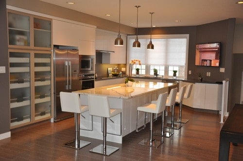 Modern kitchen featuring hardwood floors and a regular ceiling lighted by recessed and pendant lights. The center island offers a breakfast bar and has white modern seats.