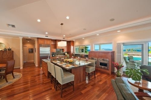 A brown kitchen featuring hardwood flooring, wooden cabinetry and kitchen counters along with a center island with a breakfast bar.