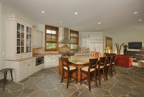 Spacious kitchen with a beautiful flooring along with a wooden center island with a marble countertop.