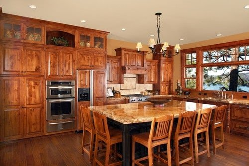 A brown kitchen with hardwood floors, wooden cabinetry and kitchen counters along with a center island with breakfast bar paired with wooden chairs.