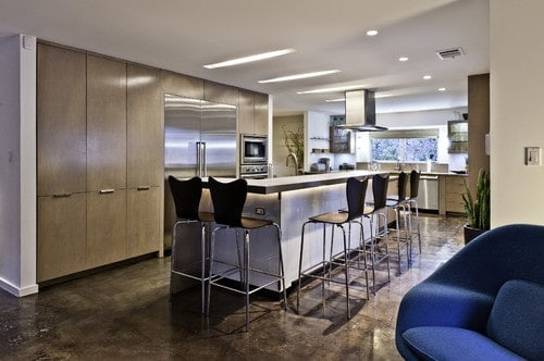 This kitchen features stunning flooring along with an island with a breakfast bar counter with modish black chairs.
