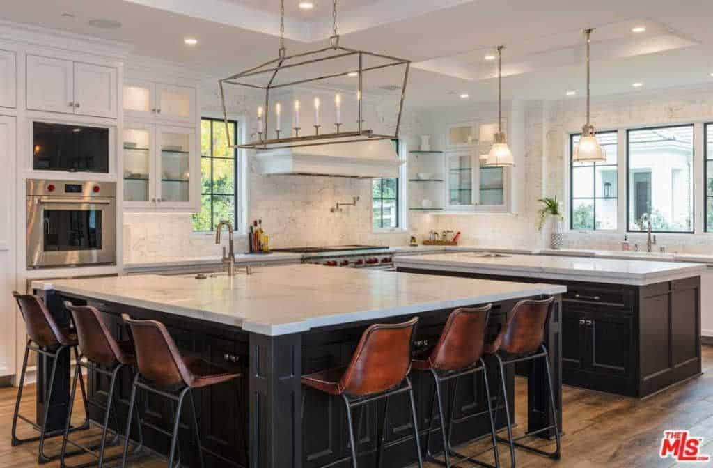 Large kitchen boasting two islands. One serves as the meal preparation island and the other one serves as a breakfast bar. These islands both have marble countertops.