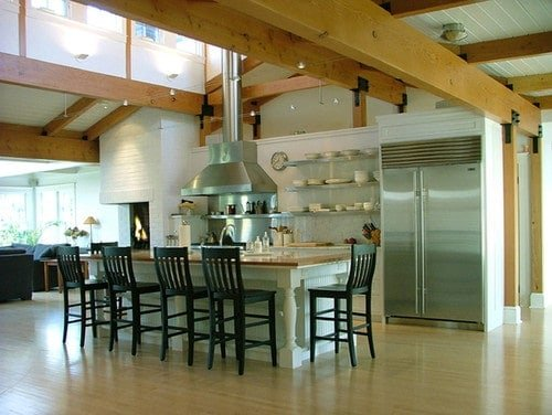 A spacious kitchen featuring a tall ceiling with large exposed beams. It also has a center island with space for a breakfast bar.