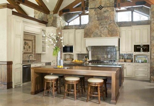 A kitchen with a tall ceiling with exposed beams and has two islands. The wooden island serves as the kitchen's breakfast bar.