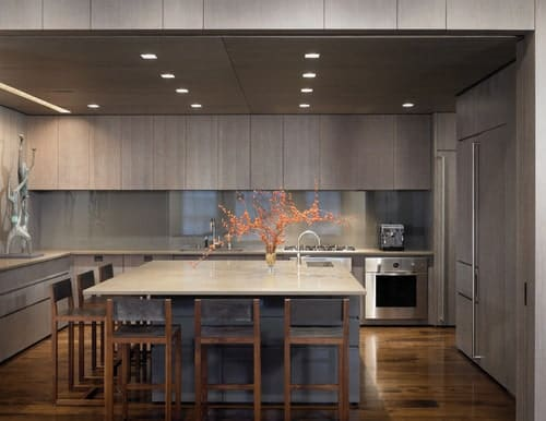 This kitchen offers a large square-type center island with space for a breakfast bar. The area is lighted by recessed ceiling lights.