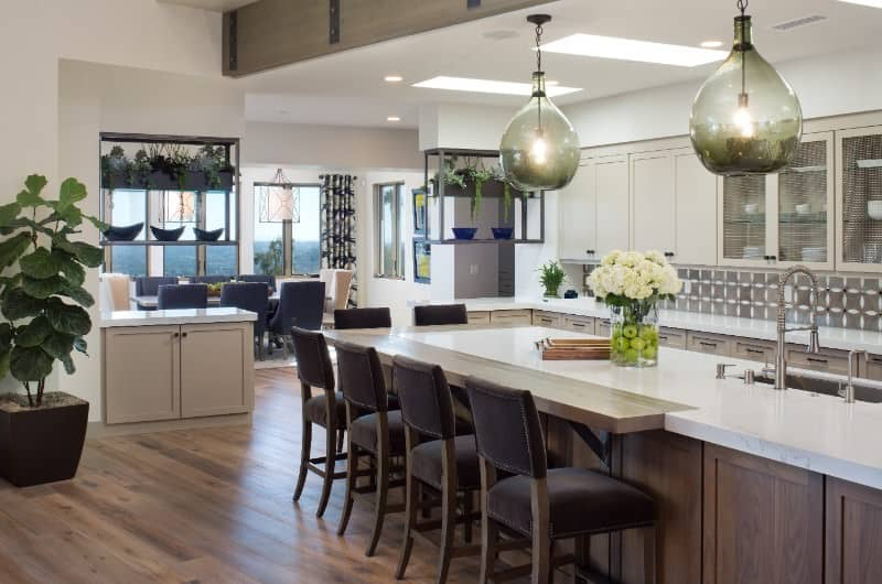This kitchen features white marble countertops on both kitchen counters and the center island. It also has a breakfast bar counter.