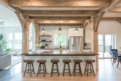 A single wall kitchen featuring a breakfast bar island for six lighted by pendant lights.