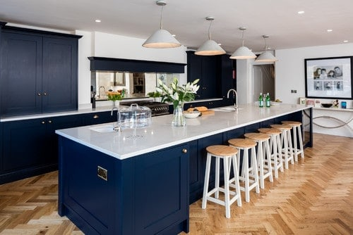 A very stylish kitchen area with herringbone-style hardwood floors along with navy blue kitchen counters and center island, both have white countertops. The breakfast bar is lighted by pendant lights.