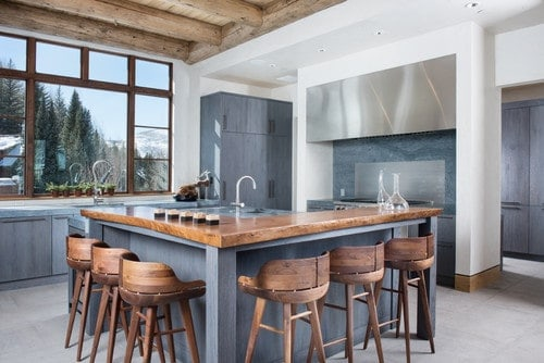 This kitchen features a brown and blueish gray color scheme and has a custom island with a wooden breakfast bar counter paired with wooden seats.