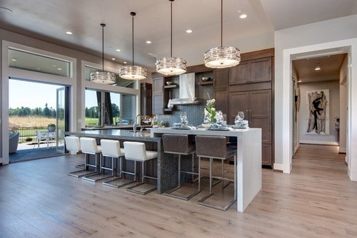 Large kitchen area featuring a center island with a breakfast bar along with additional breakfast bar counter for two on it side. This kitchen is lighted by large pendant lights and recessed lights.