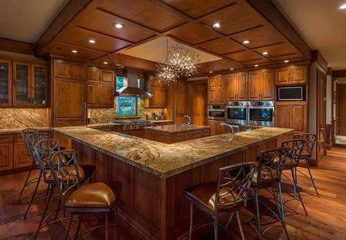 A large brown kitchen featuring a small center island lighted by gorgeous ceiling lights. This kitchen also offers a long breakfast bar for eight.
