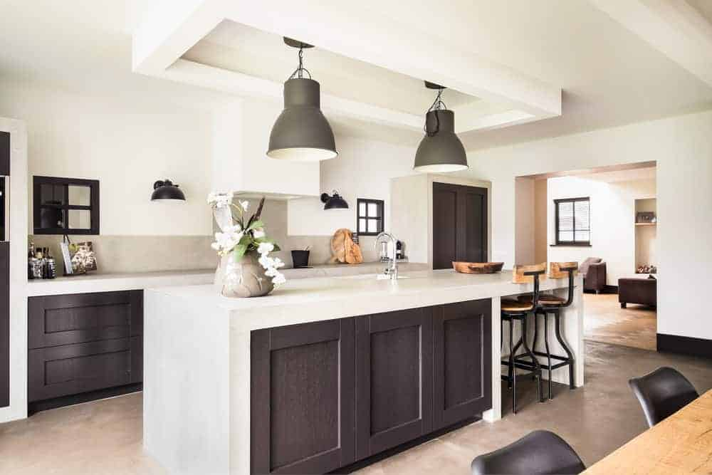This kitchen features a lovely center island with a white waterfall-style countertop and has space for a breakfast bar. The area is lighted by two large pendant lights.