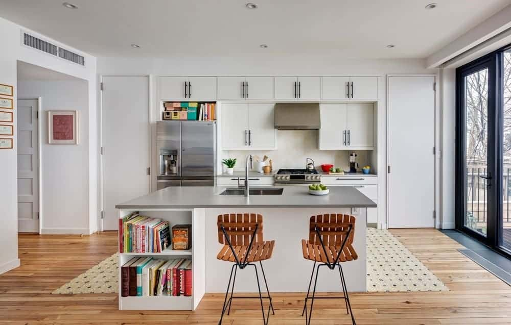 A single wall kitchen featuring a breakfast bar island for two. The island has built-in shelving below.