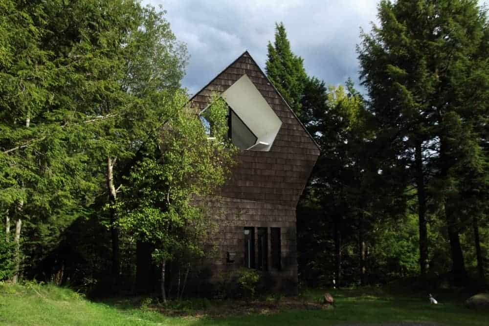 This home is set in the middle of the woods full of large and mature trees. It features a black exterior.