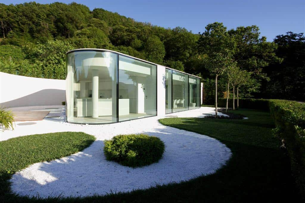A small contemporary house with glass walls and has a beautiful garden area.