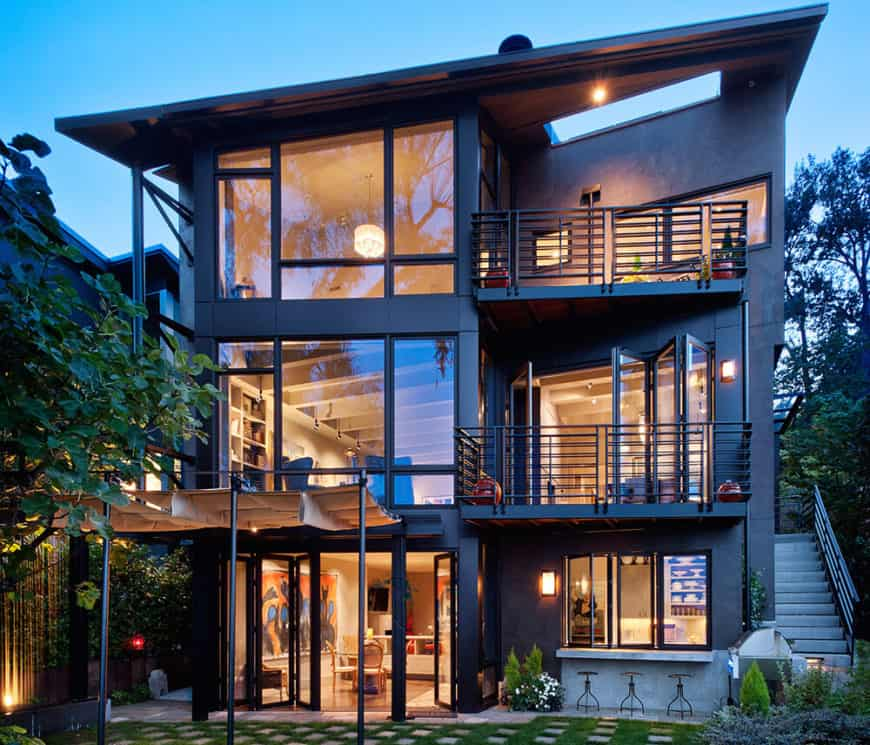 A contemporary residence featuring a black exterior with large glass windows along with two balconies.