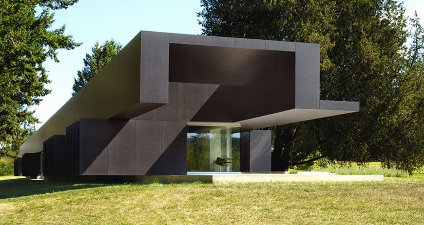 A long and large modern house with a black exterior. It has an amazing interior as well.