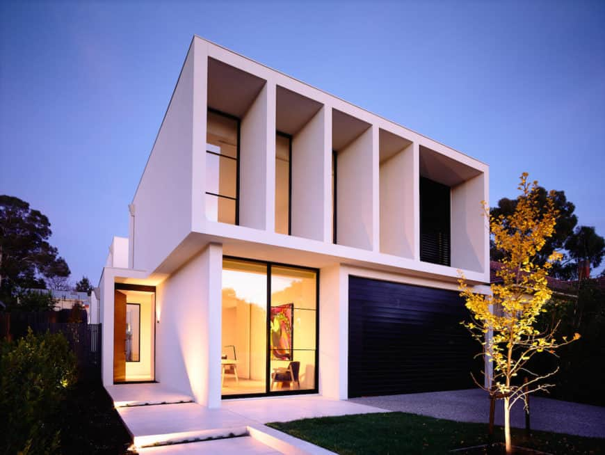 Contemporary house featuring a white exterior. It has a small garden area with a beautiful walkway along with a narrow driveway leading to the garage.