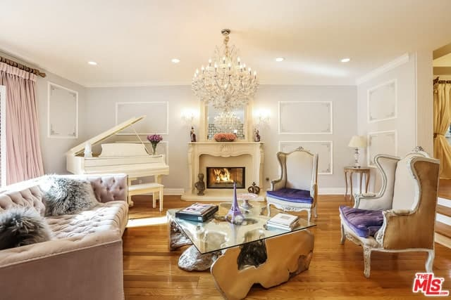 Mediterranean-style living room interior with a chandelier, grand piano, fireplace, and hardwood flooring.