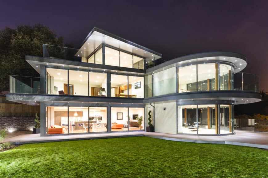A contemporary house featuring glass walls and windows. It has a balcony with glass railings as well.