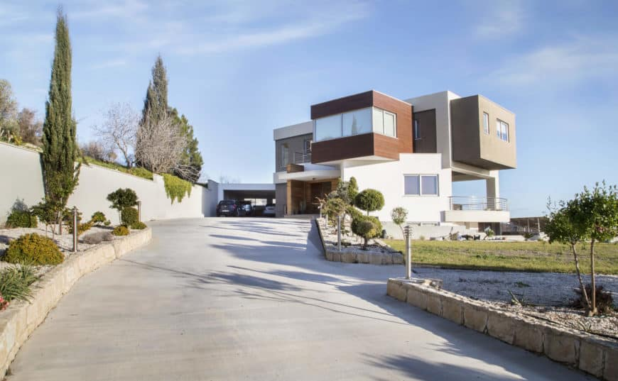 Large contemporary house with a wide, two-way driveway. There's a sprawling lawn area as well.