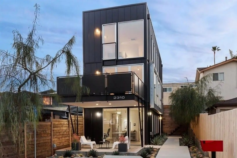 A modern industrial home featuring a black exterior, a nice walkway and a great patio area.