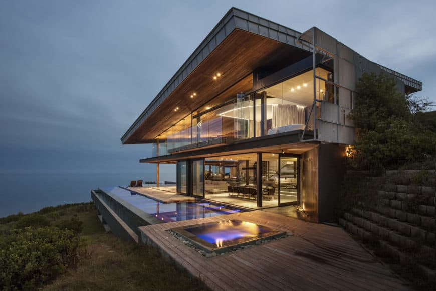 A contemporary house with mixed of wood and glass exterior. It also has an infinity pool that offers a breathtaking view of the surroundings.