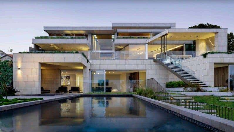 A stunning contemporary home designed by SAOTA. It features many outdoor amenities including a swimming pool and a well-maintained lawn area.