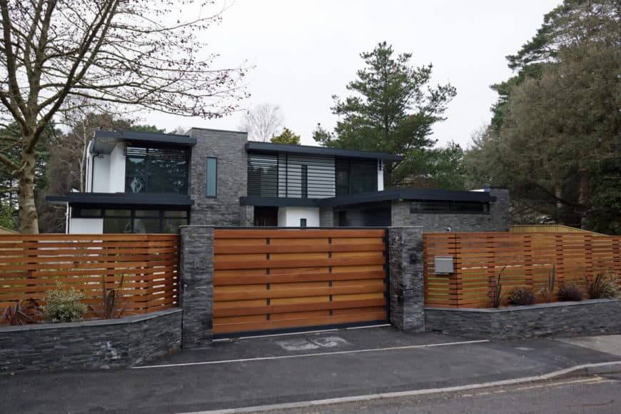 A stylish contemporary house with a wooden fence that looks modish.