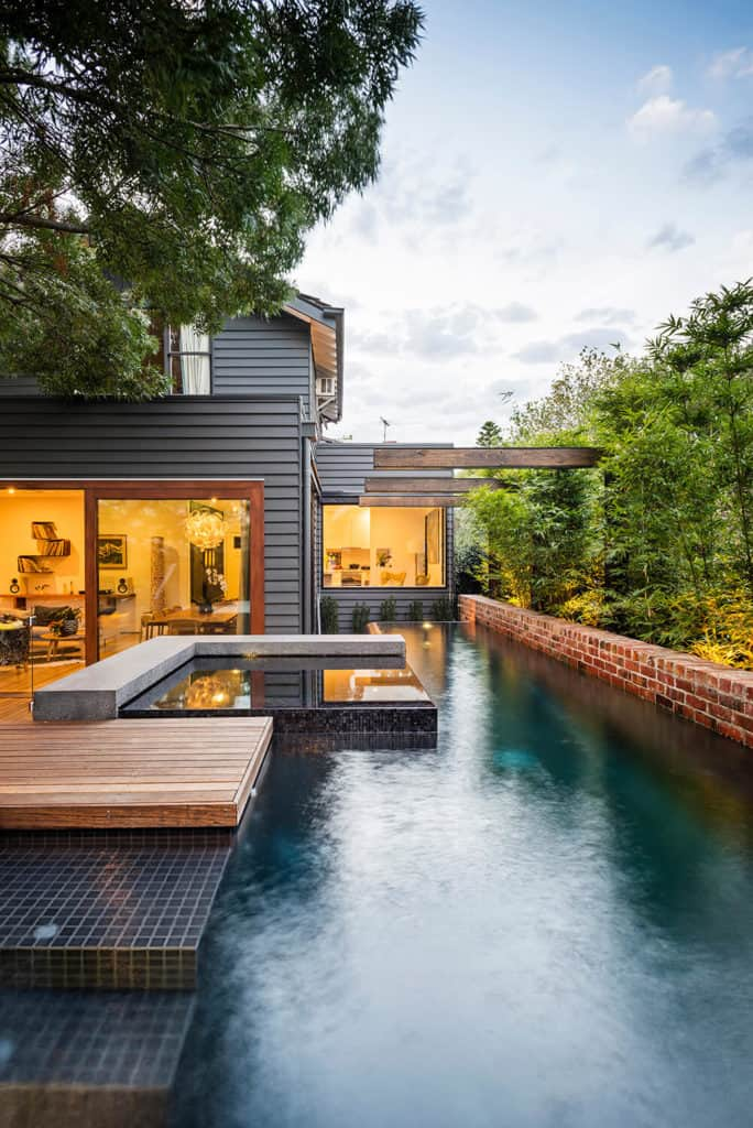 This house has a black exterior and it offers a nice swimming pool and a deck.