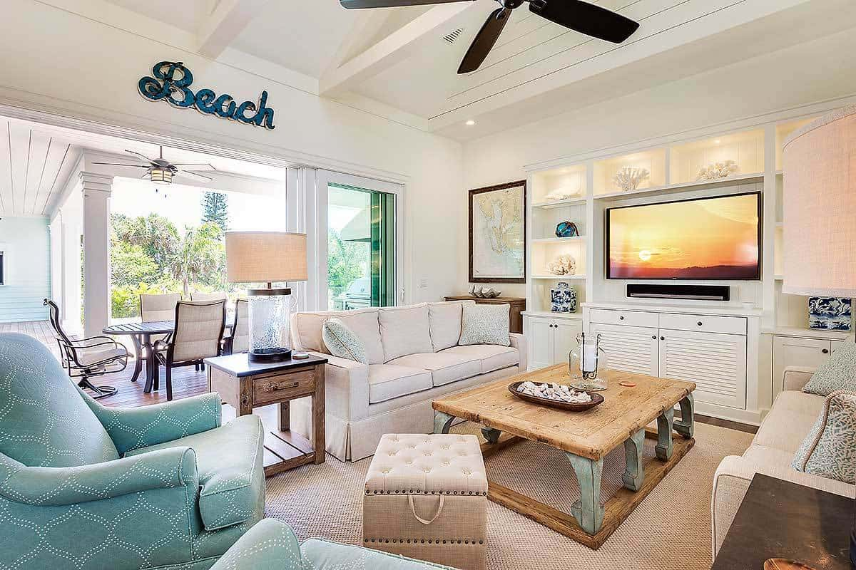 Beach-style living room interior with beam ceiling, white walls, and built-in shelving.