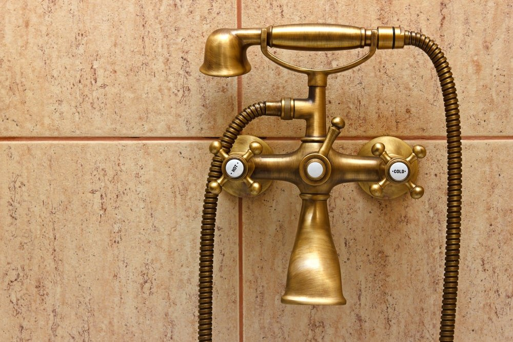 Bronze bathroom faucet mounted on the tiled wall.