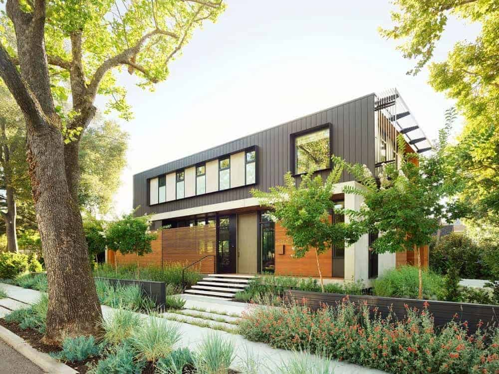 This modern house features a black, white and brown exterior along with multiple plants and trees.