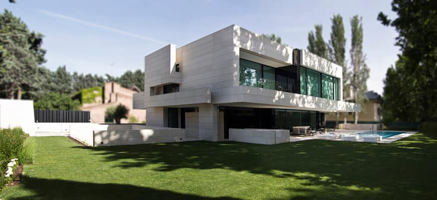 This contemporary home features a large outdoor area with a sprawling lawn area along with a swimming pool.
