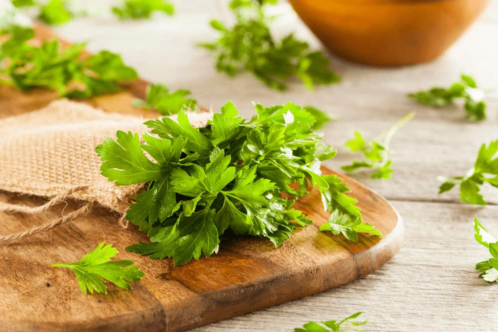 Parsley in a jute bag on a wooden chopping board.