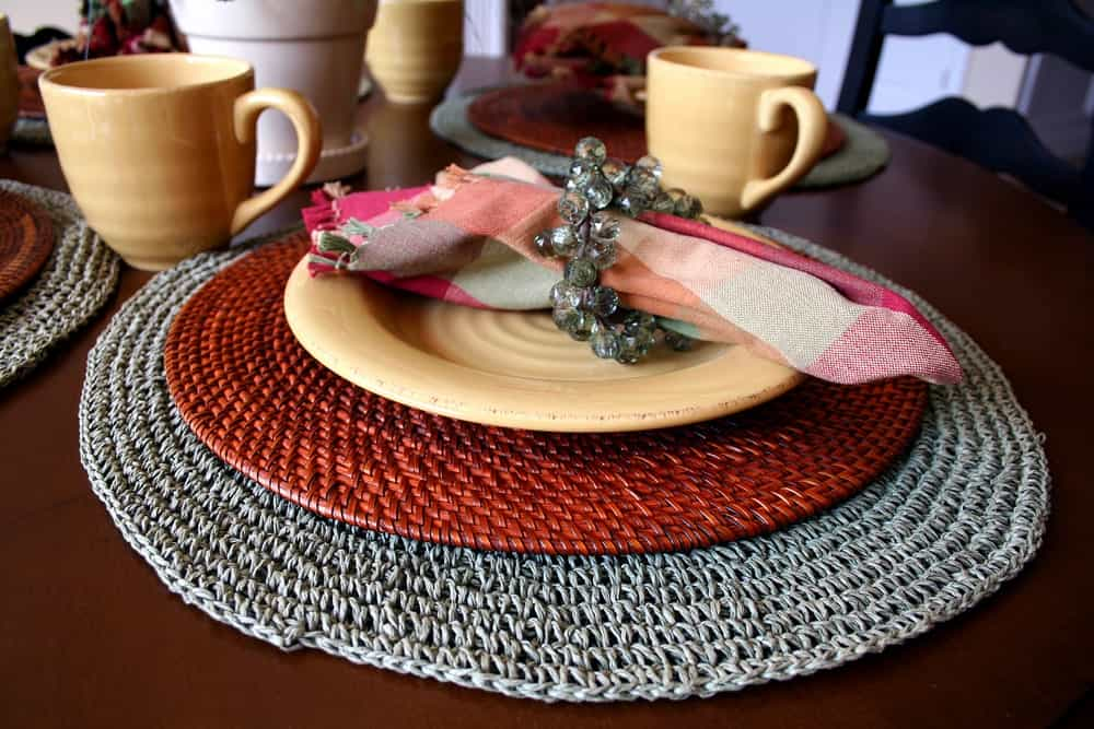 Round woven placemat in earth tones with yellow crockery.