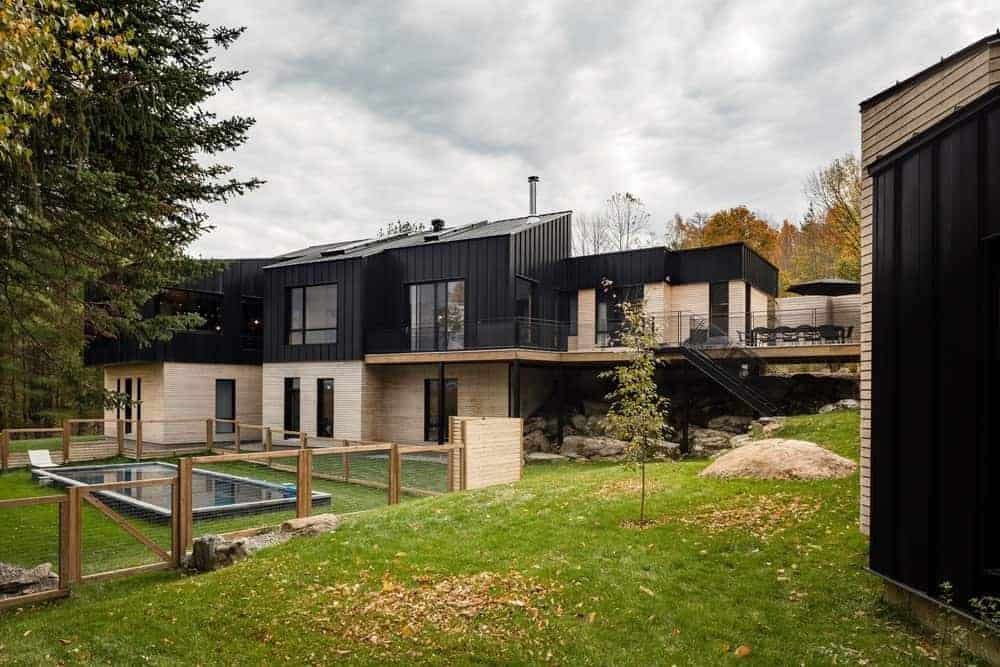 This black house has a creative outdoor amenities and has a beautiful lawn area.