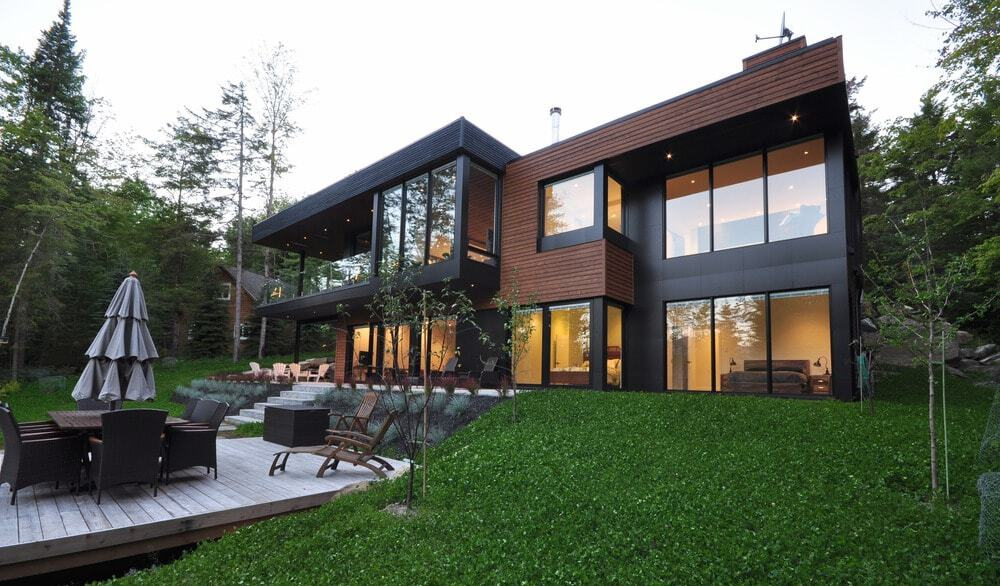 A stylish contemporary house featuring a deck with an outdoor dining and multiple sitting lounges.