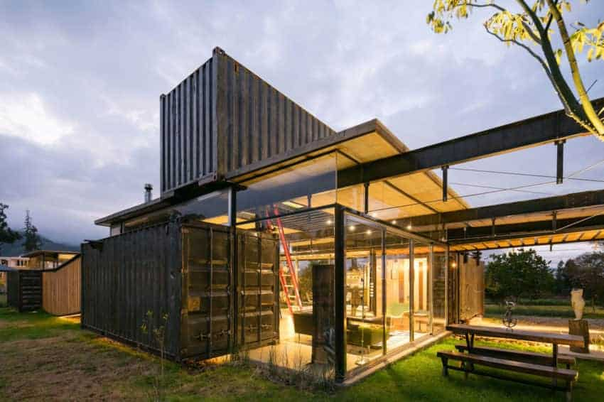 A black container home with nice outdoor areas and well-maintained lawns.